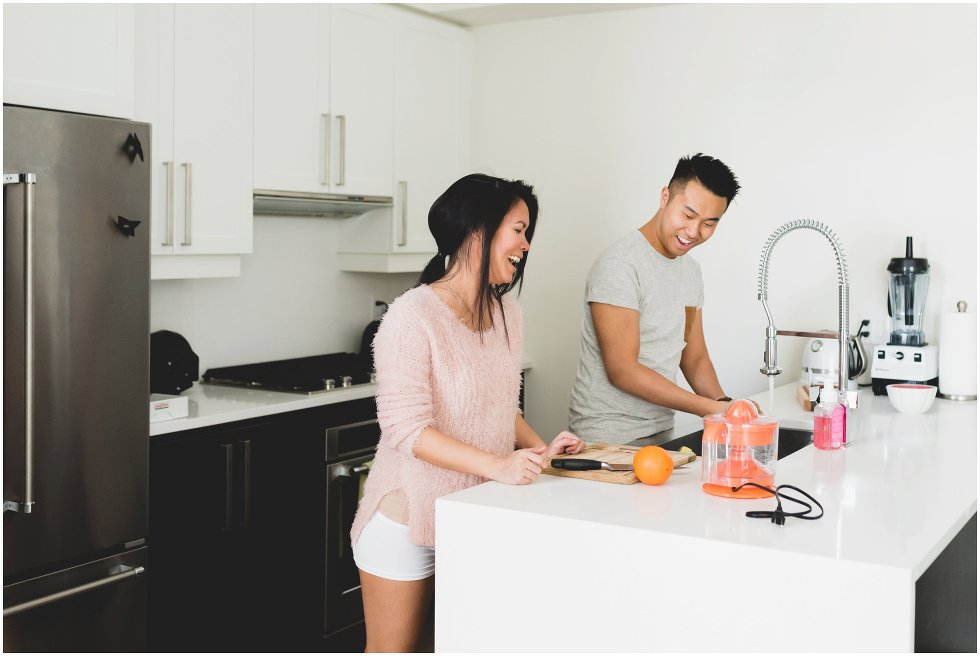Couple making orange juice during their Toronto lifestyle maternity photos.