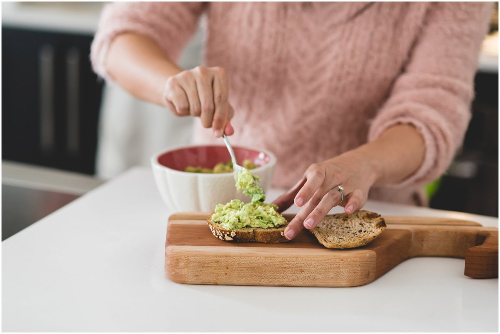 Woman smearing avocado on toast.
