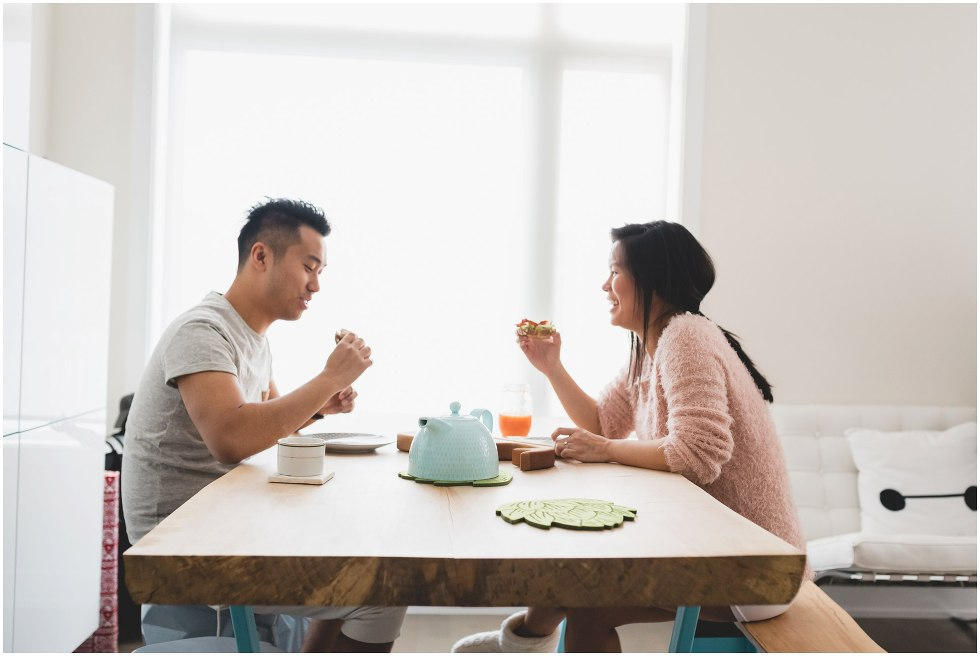 Husband and wife eating lunch during their Toronto lifestyle maternity photos.