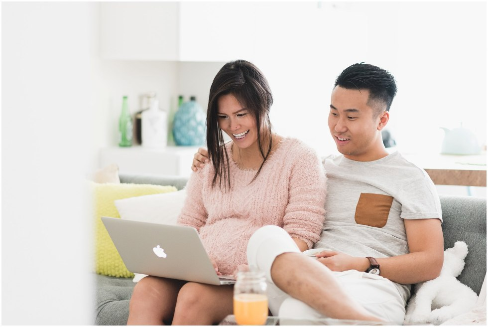 Husband and wife look at baby registry online.