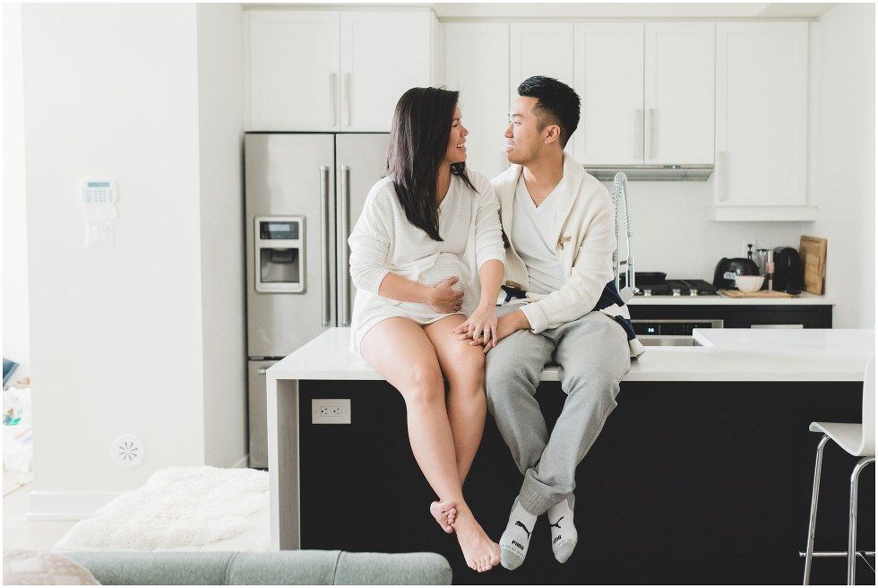 Married couple sitting on the kitchen counter, during their Toronto lifestyle maternity photos.