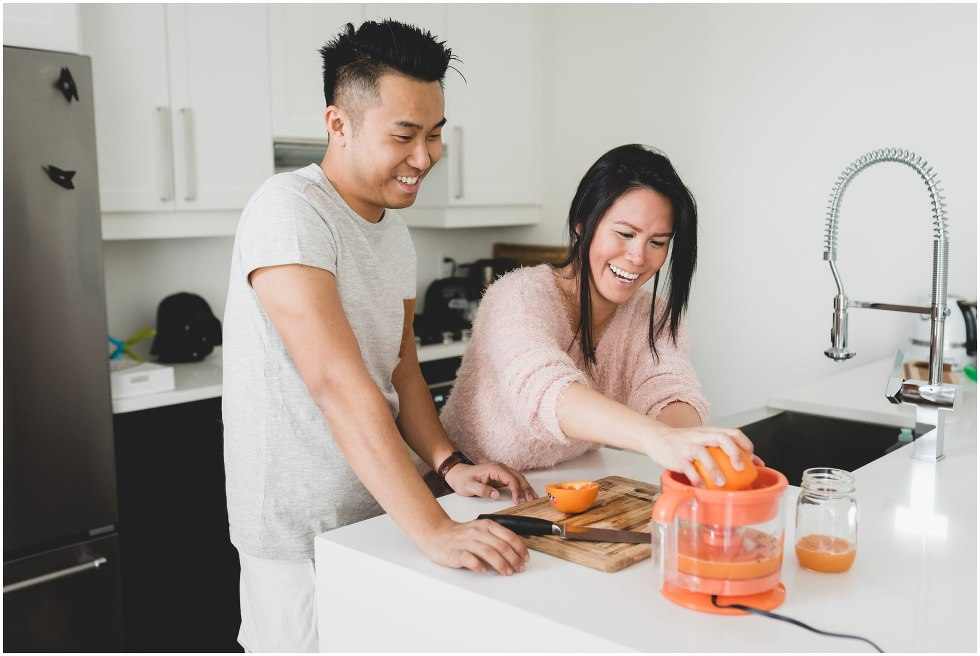Couple squeezing oranges to make orange juice, during their Toronto lifestyle maternity photos.
