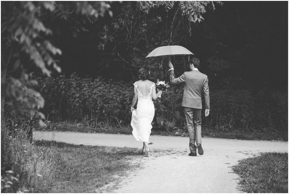 Groom holding and umbrella for the bride as they walk at Goldie Mill Ruins