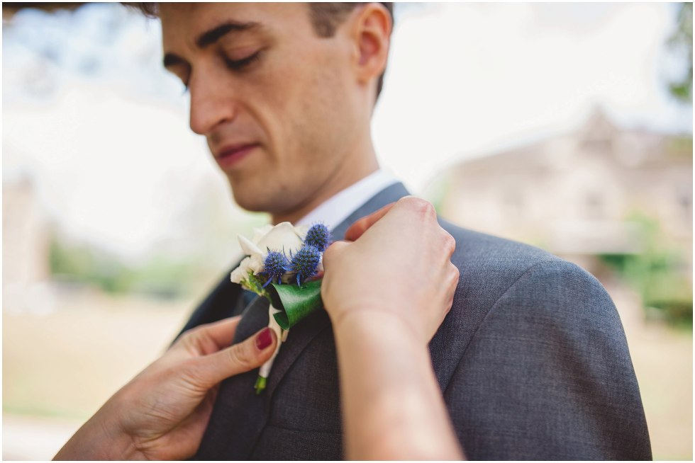Groom getting his boutonniere put on