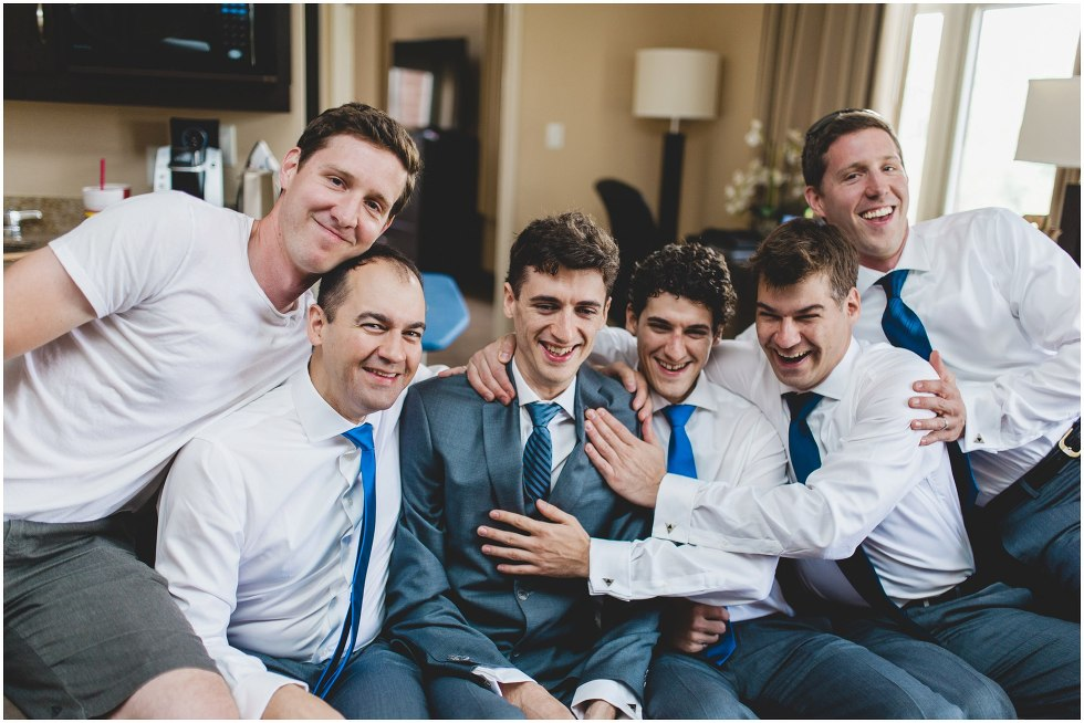 Groomsmen squished on a couch with the groom laughing and smiling