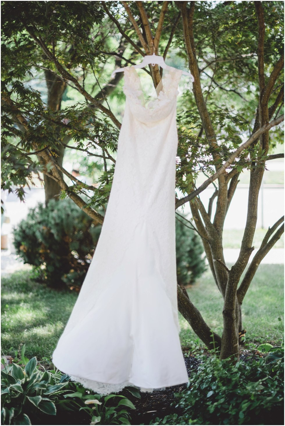 Brides dress swaying in the wind as it hangs from a tree