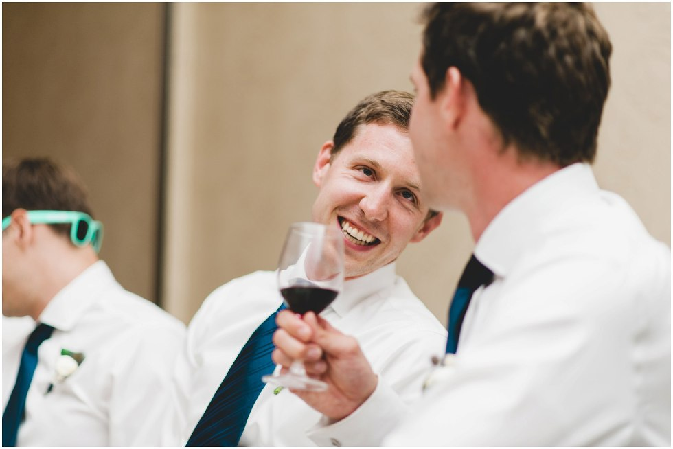 Candid moment of groomsmen chatting to a friend