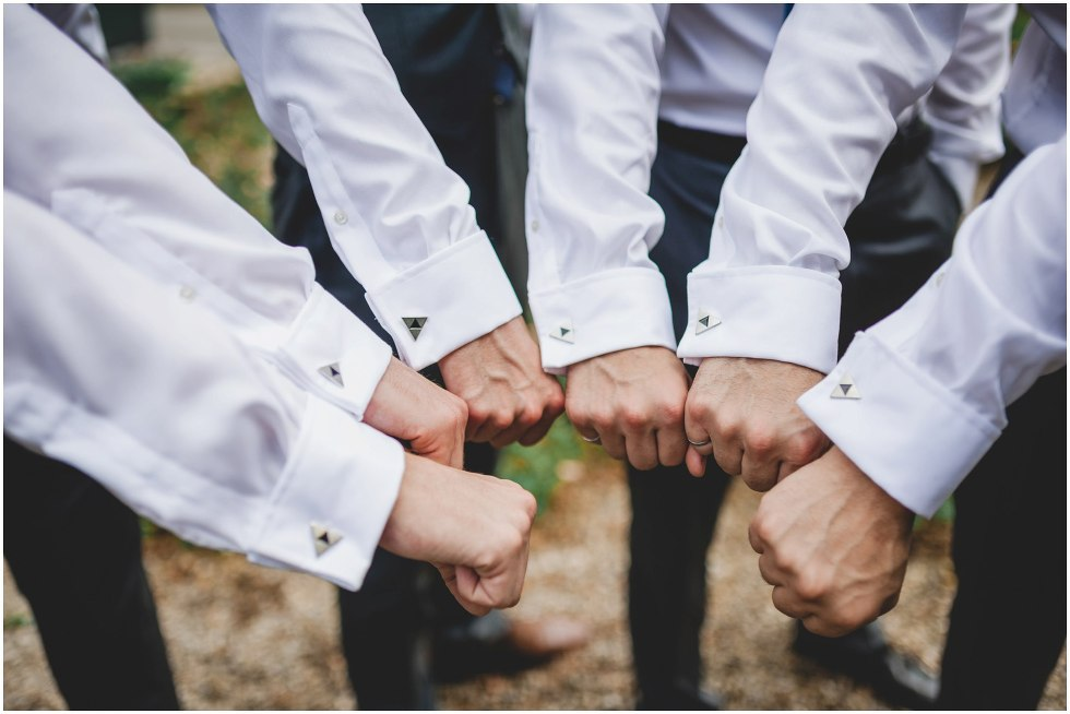 Groomsmen holding hands closely together to show cufflinks