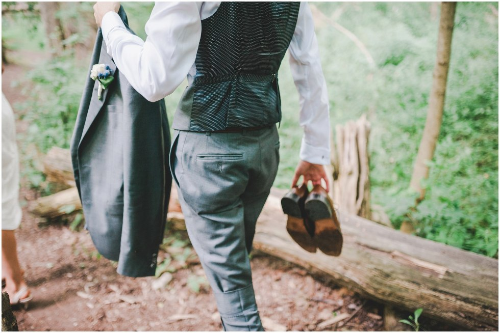 Groom walking while carrying shoes