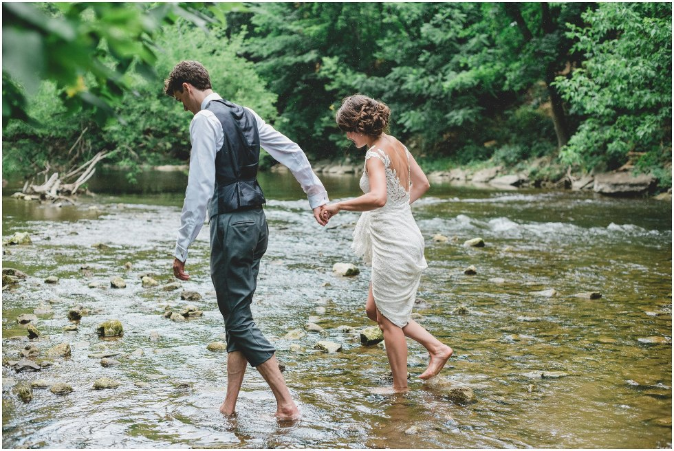 Bride and groom walking across the river
