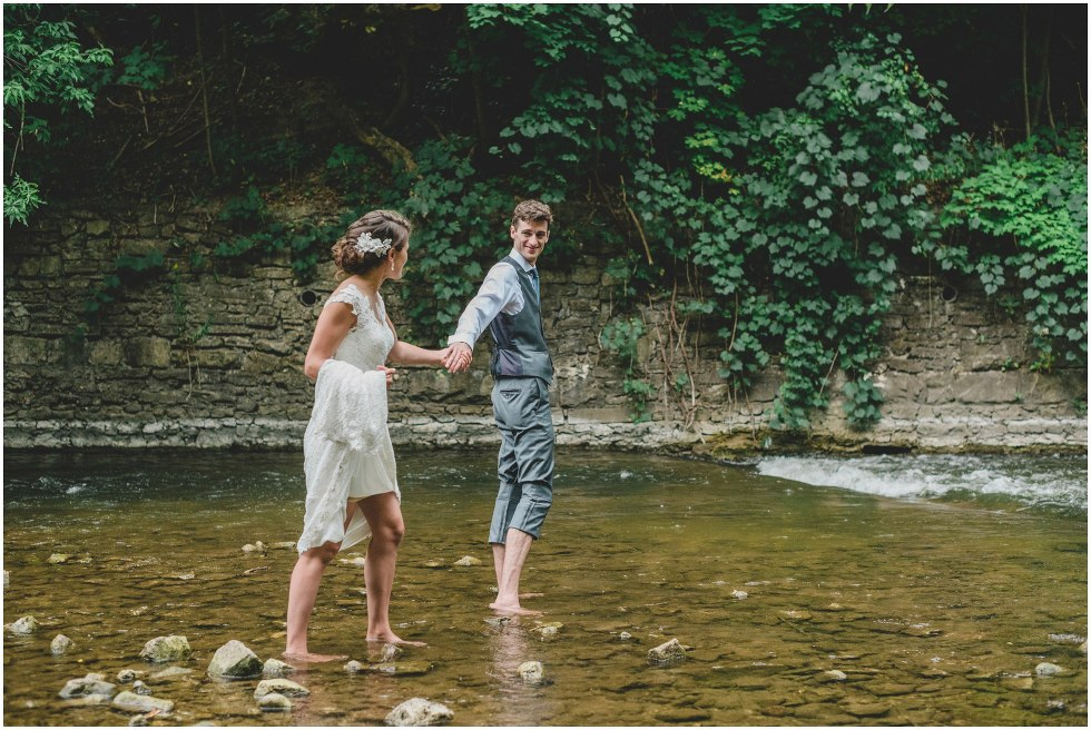 Bride and groom walking barefoot in the river