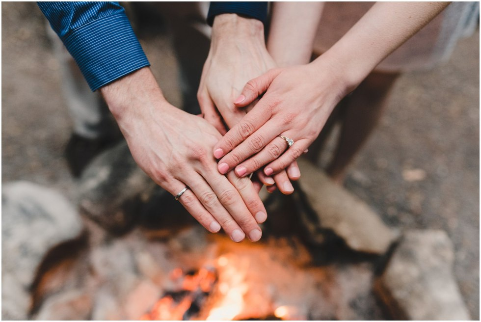 Couple warming hands over the fire