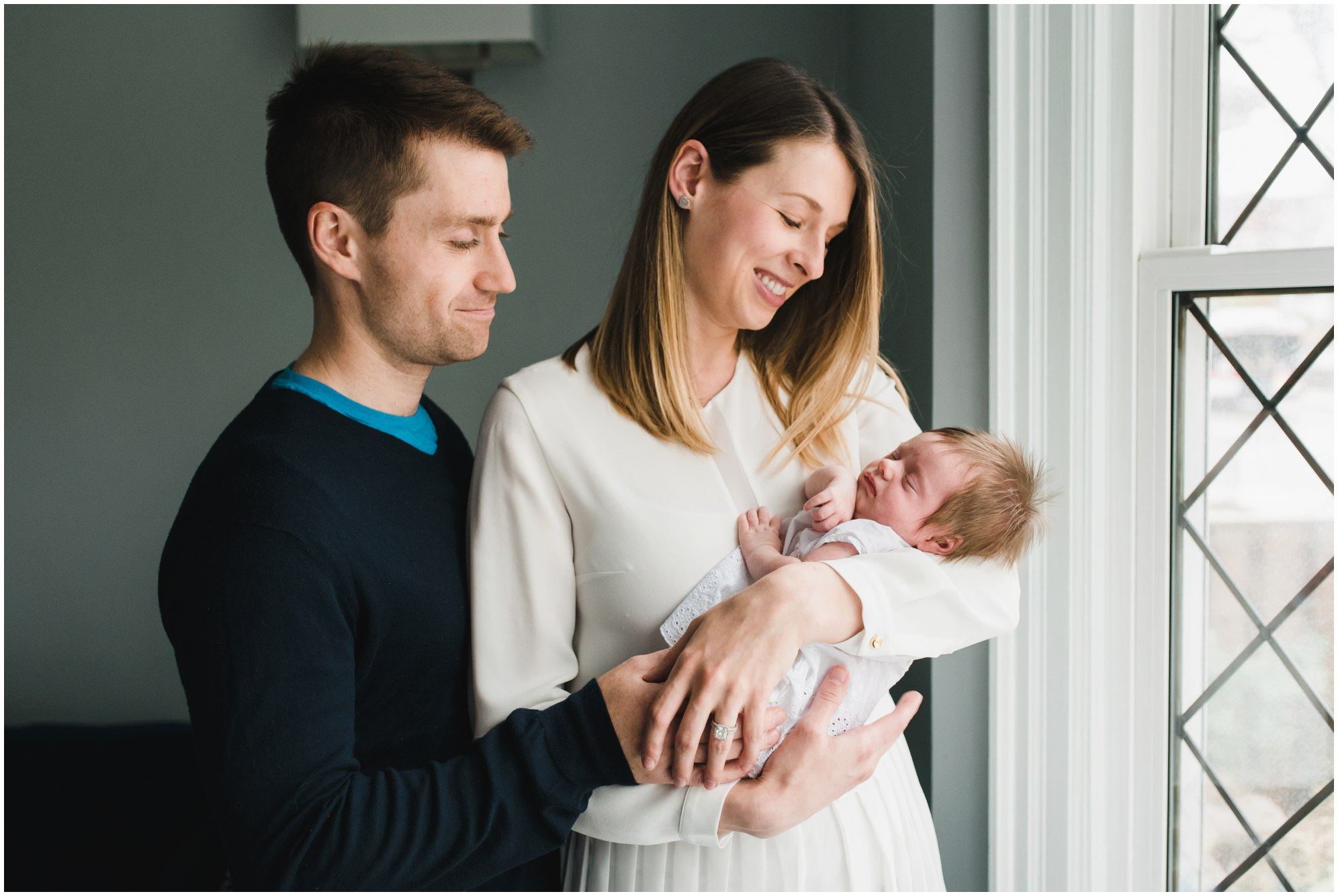 Parents holding and smiling at their daughter during their Toronto Newborn Lifestyle photos