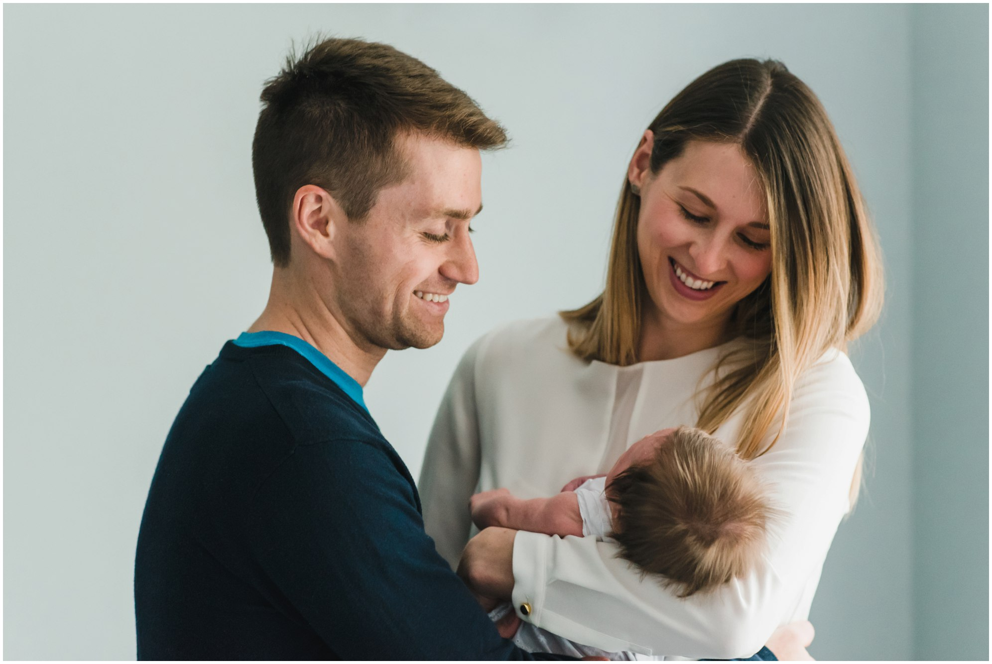 Parents smiling and holding their daughter during their Toronto Newborn Lifestyle photos