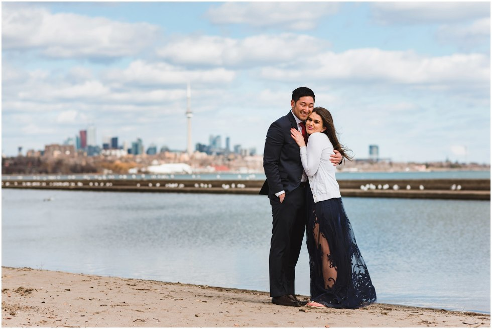 couple hugging on a beach with Toronto skyline in background proposal photographer Gillian Foster