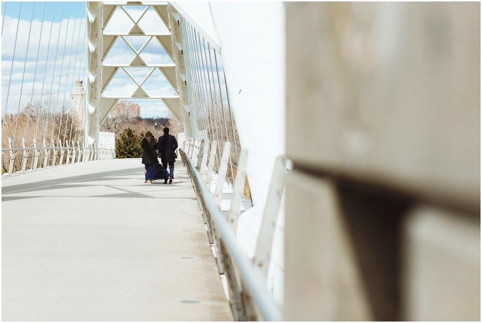 couple walking across white bridge Toronto engagement photographer