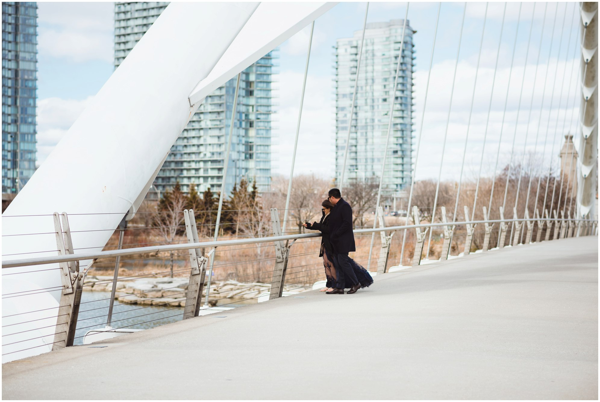 couple standing together on white bridge with condo buildings in background Toronto proposal photography