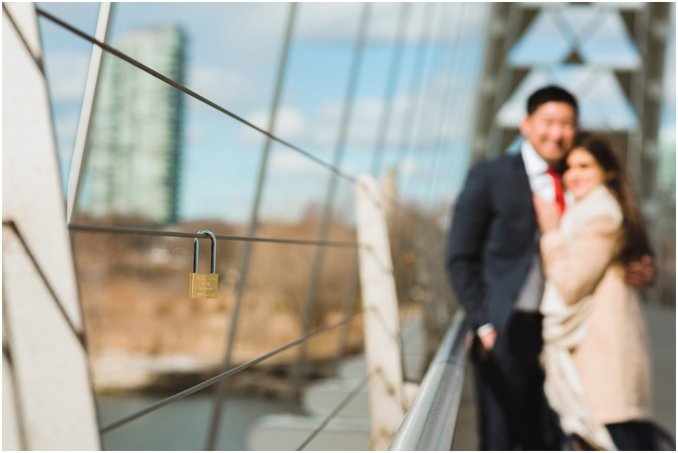 lock placed on bride railing with couple looking on Toronto proposal photographer Gillian Foster
