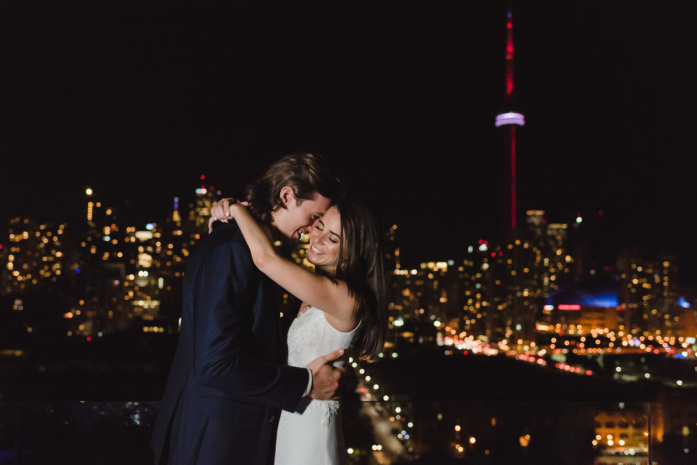 bride and groom in loving embrace with nighttime skyline of downtown Toronto in the background Gillian Foster wedding photography