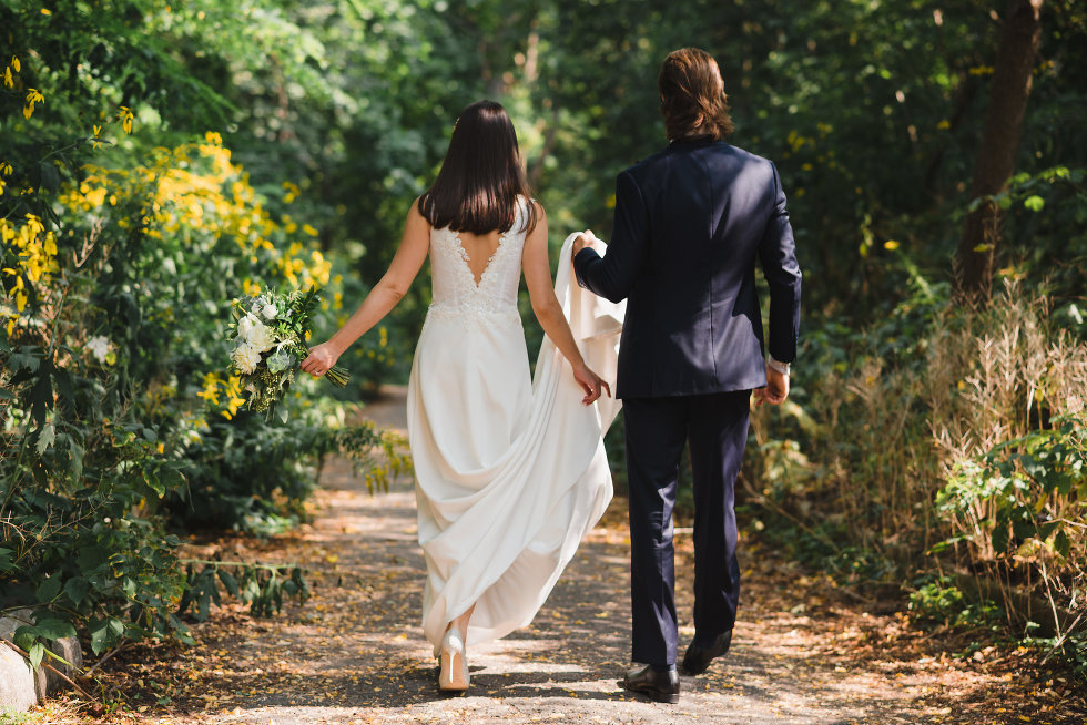 bride and groom holding hands as they walk through forest Toronto wedding photography