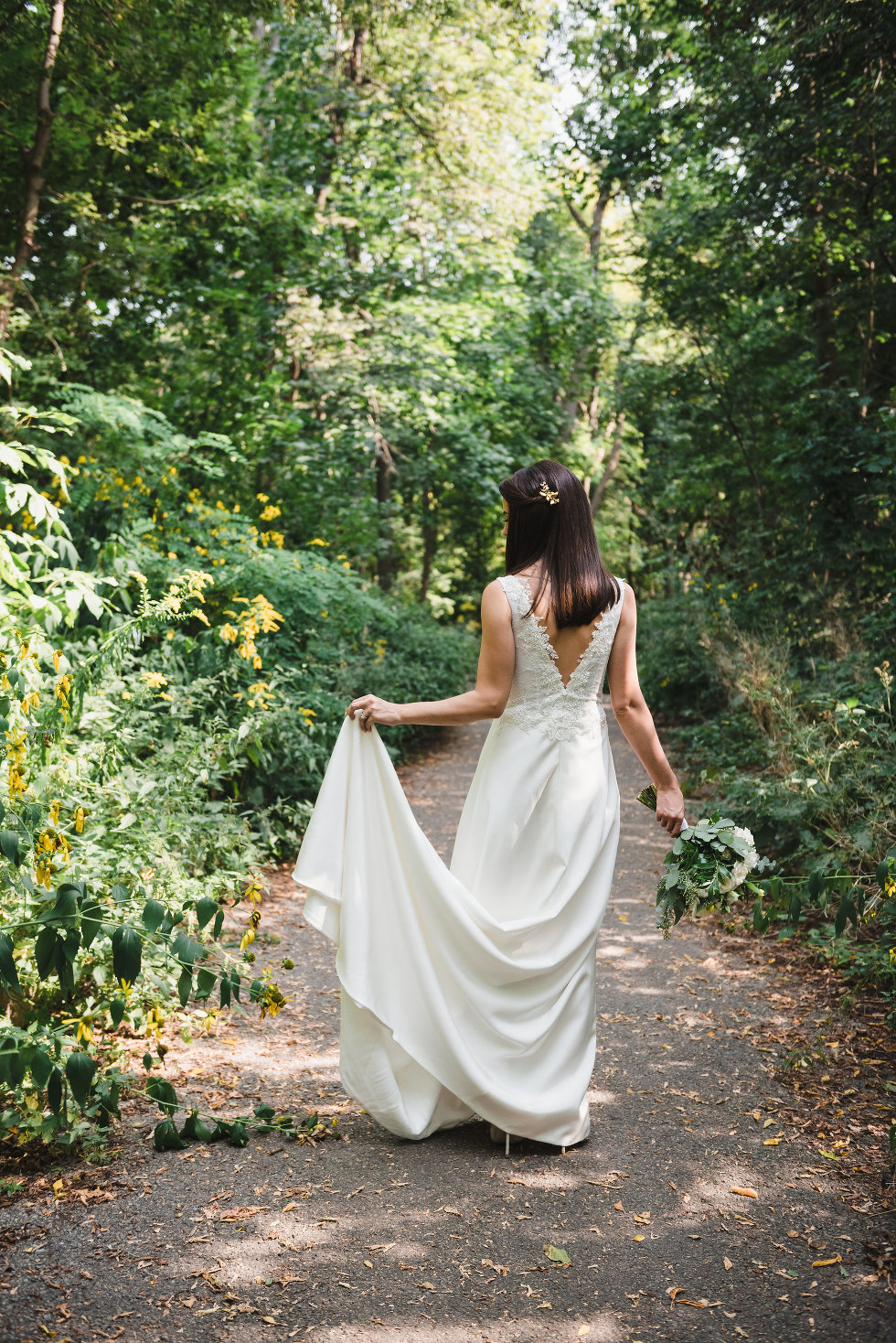 bride holding up bottom of wedding dress in one hand, bouquet in the other, as she walks through forest Toronto wedding photography