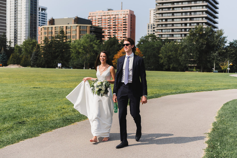 bride and groom walking along pathway in park with tall buildings in the background Toronto wedding photography