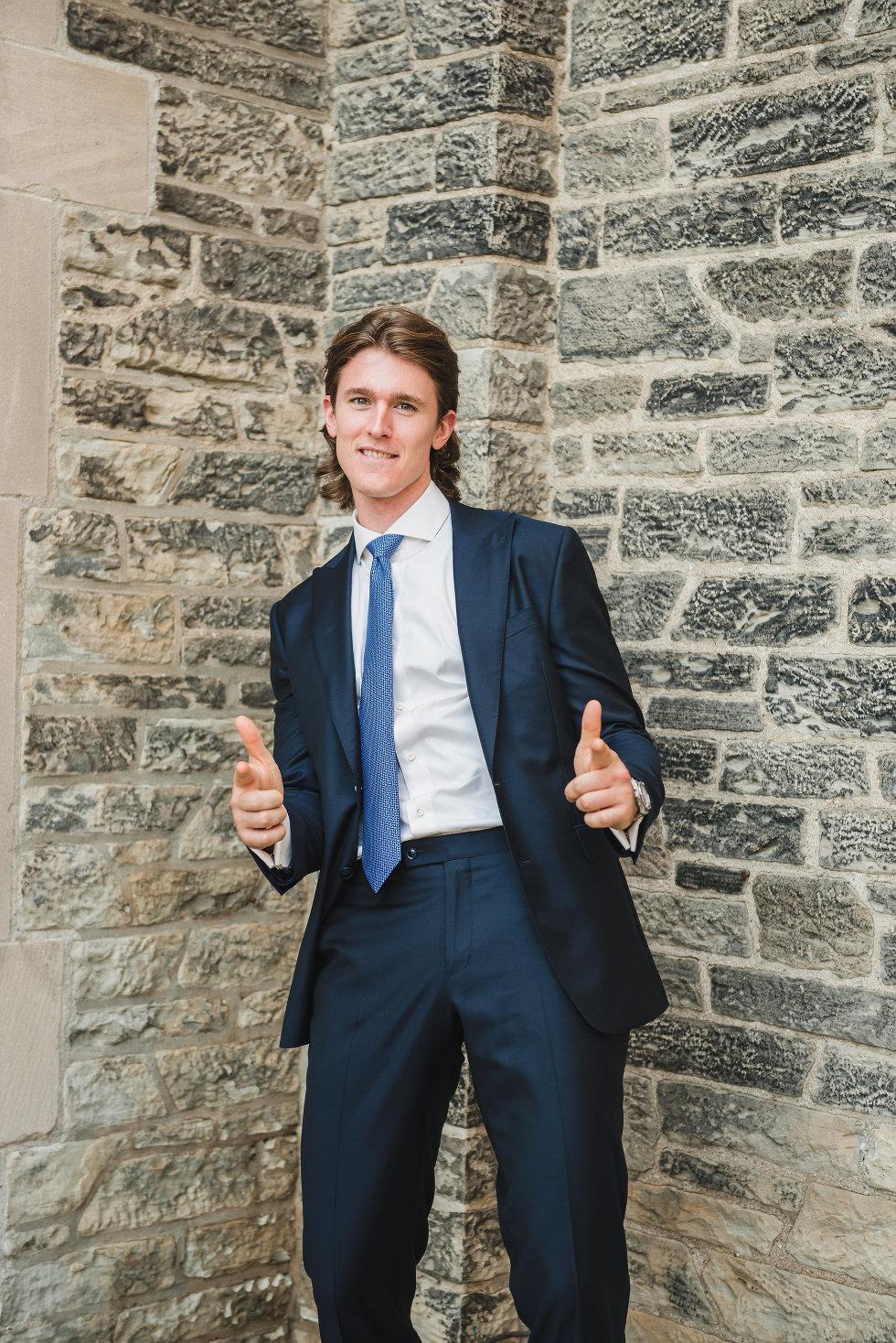 groom in front of brick wall shooting guns at camera Toronto wedding photography