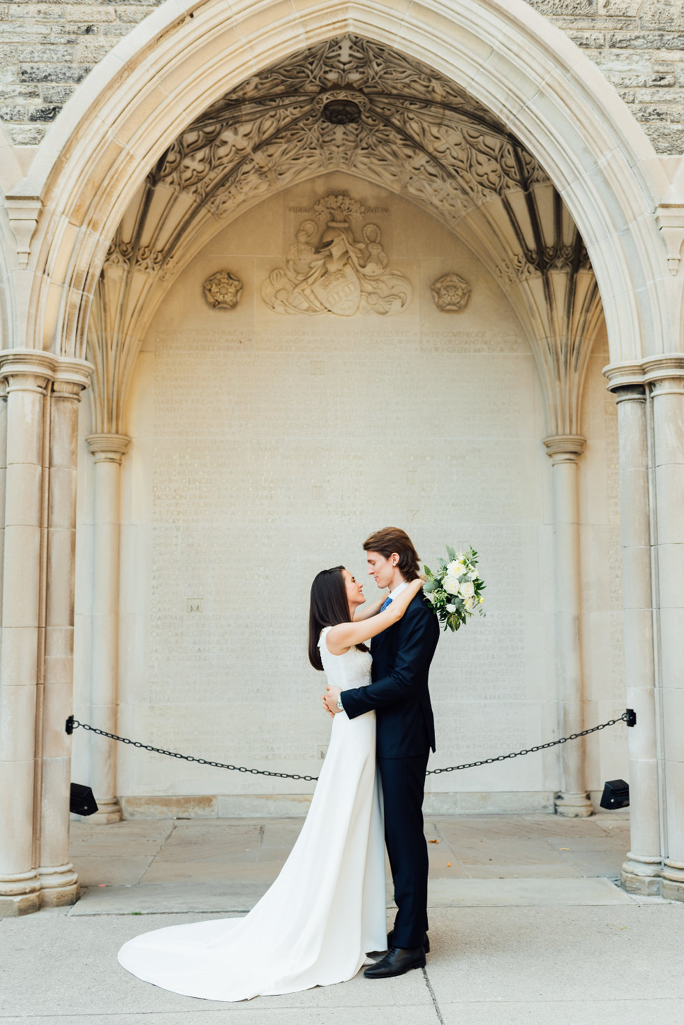 bride and groom stand together under archway of church Toronto wedding photography