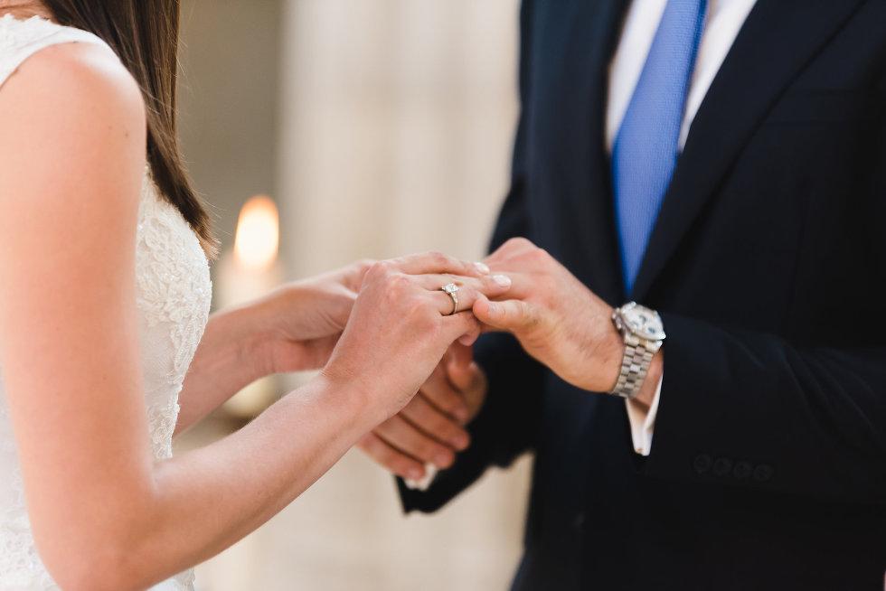 bride placing ring on grooms hand Toronto wedding photography