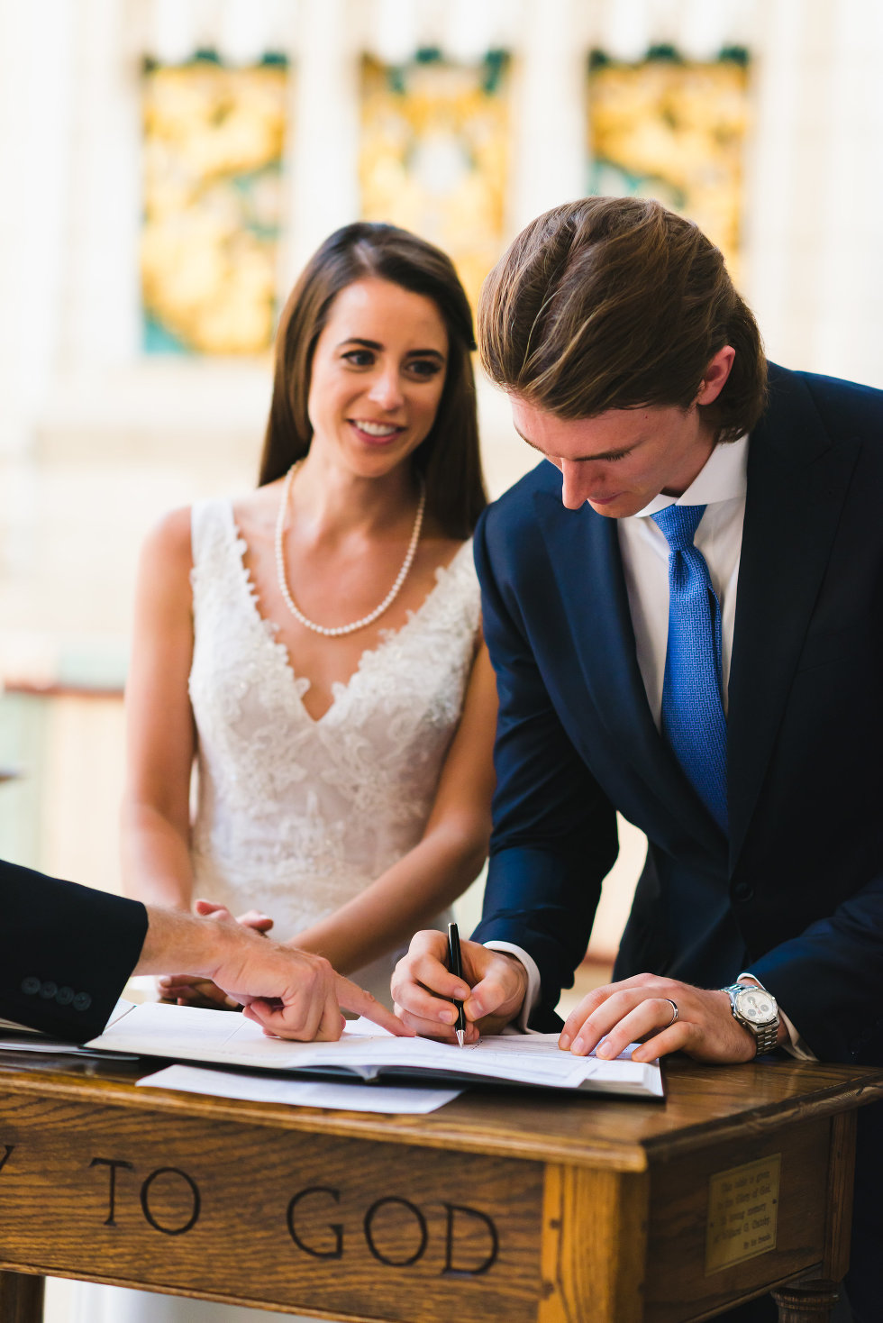 groom signing marriage certificate while bride watches him Toronto wedding photography