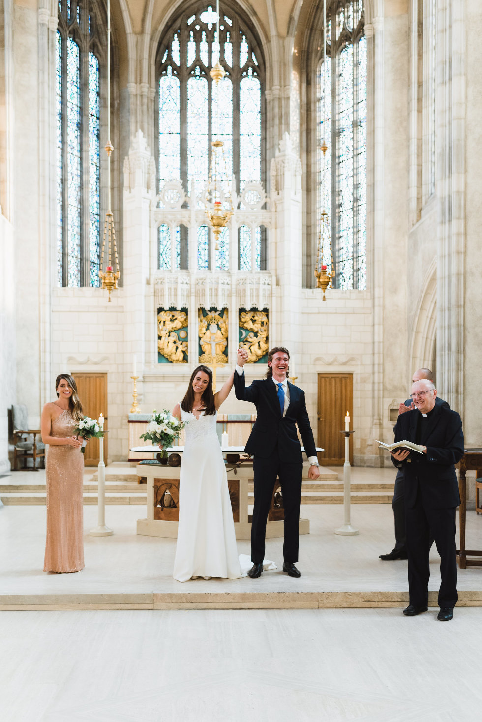 bride and groom holding hands in the air together in celebration before church guests Toronto wedding photography