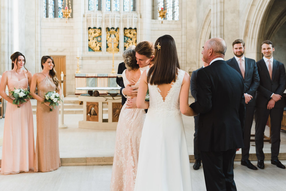 parents of the bride presenting her to the groom while wedding party stands behind them at Trinity College Chapel in Toronto
