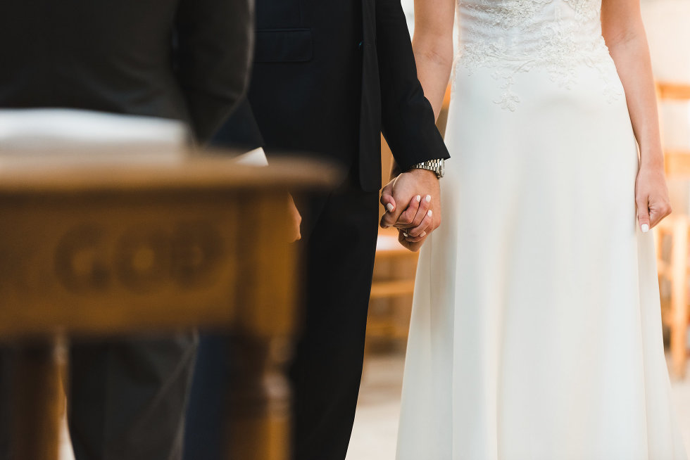 closeup of bride and grooms holding hands during ceremony at Trinity College Chapel in Toronto