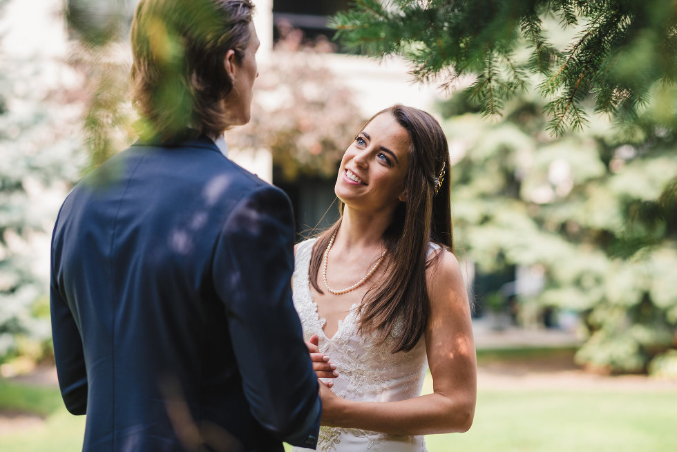 bride and groom smiling at each other surrounded by trees and garden Toronto wedding photography