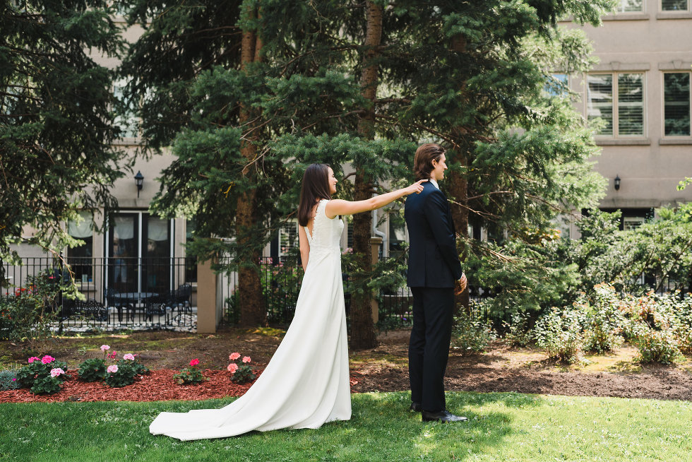 bride approaches groom from behind and taps him on shoulder Toronto wedding photography