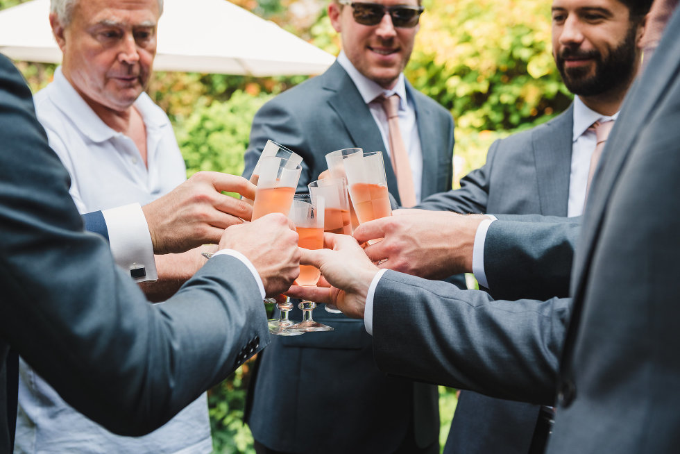 Groom and his wedding party toasting with cocktails in flutes Toronto wedding photographer