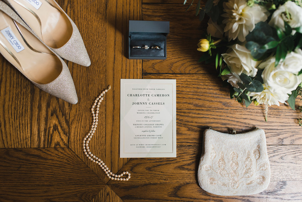 overhead shot of wedding pearls, rings, shoes, invitation, and bouquet Toronto wedding photographer