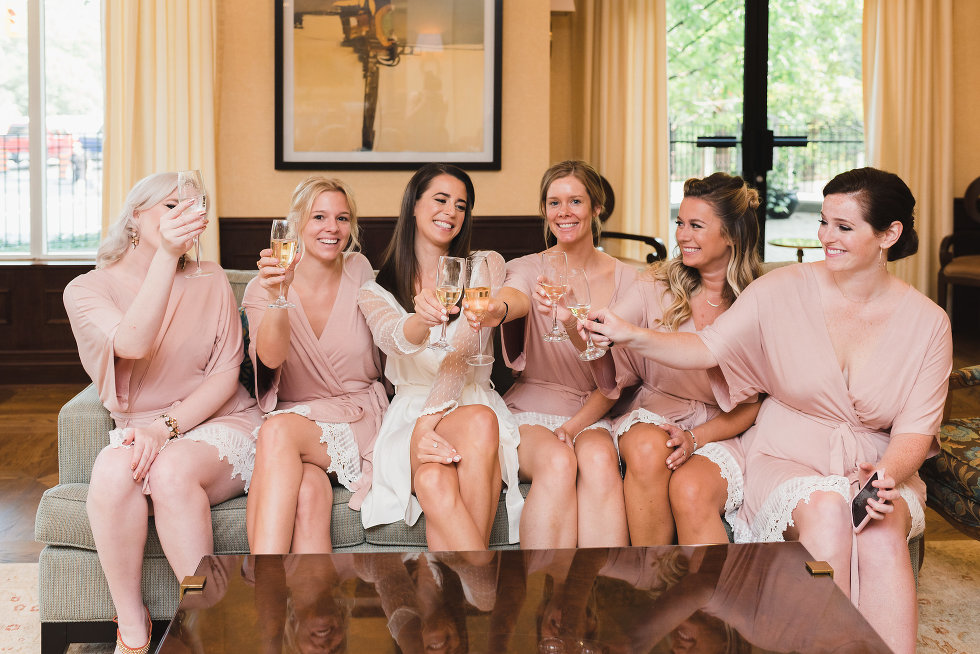 bride and her wedding party in peach robes sitting on couch and toasting with champagne Toronto wedding photographer