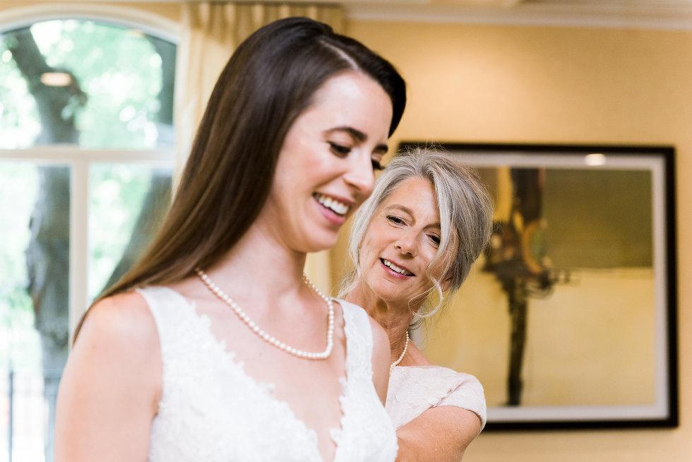 mother of bride helping bride do up dress Toronto wedding photographer