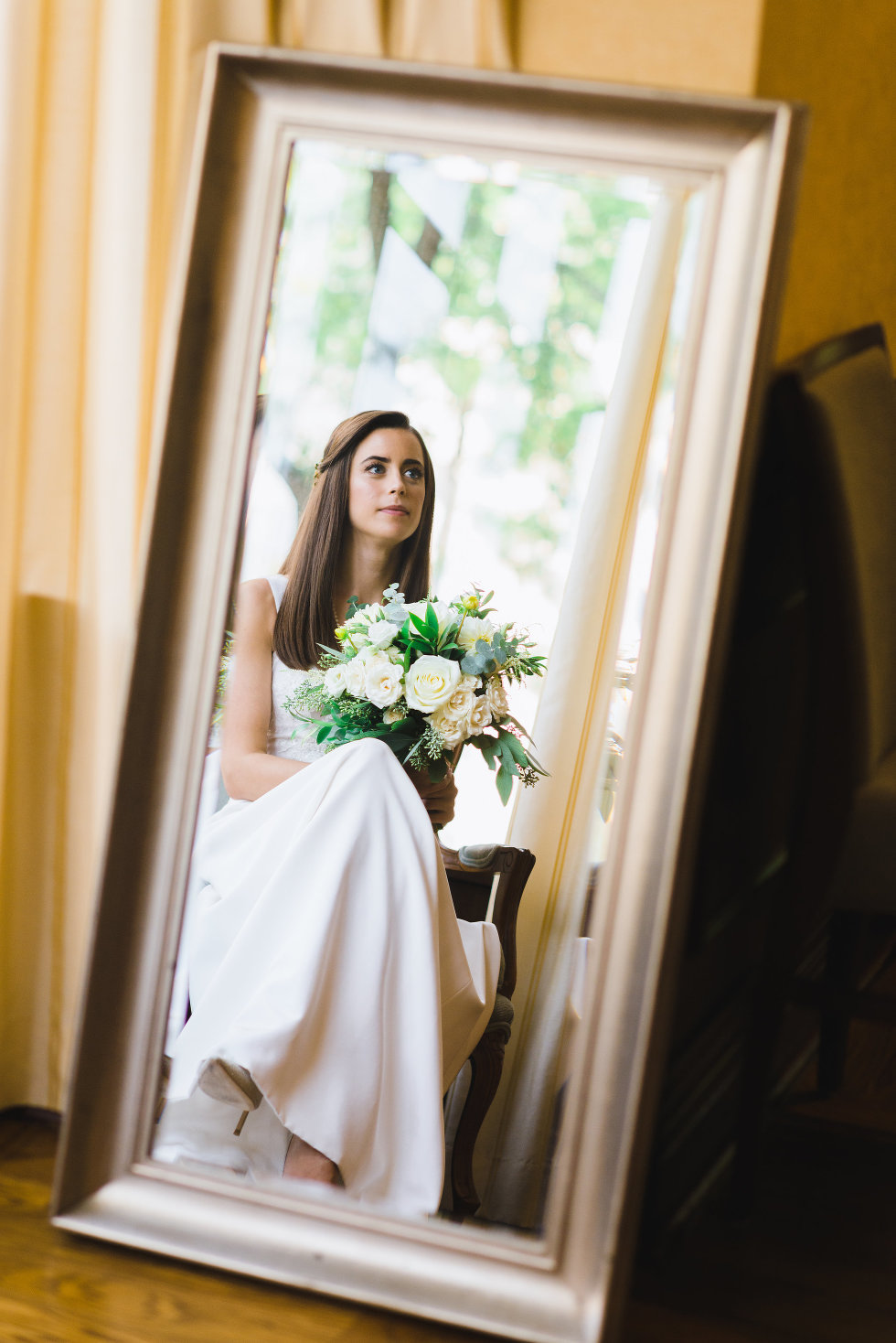 reflection in mirror of bride seated in wedding dress with bouquet Toronto wedding photography