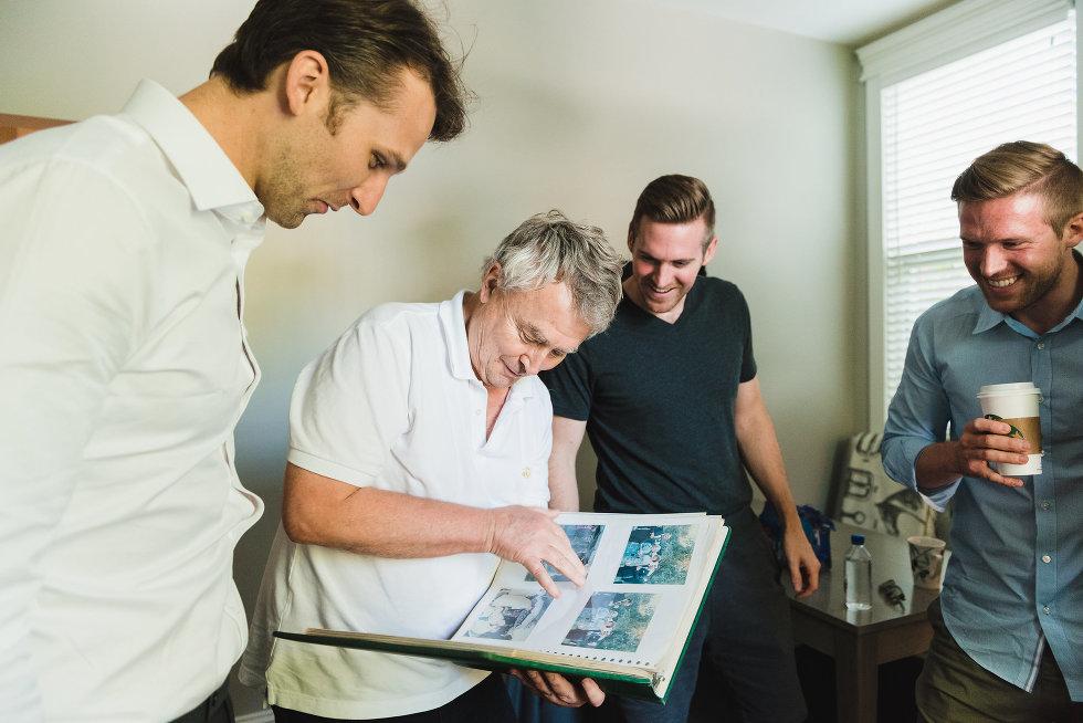 men standing around looking at old photo album