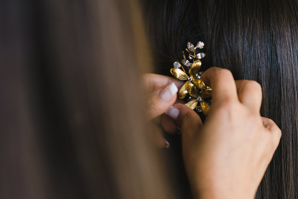 gold and diamond flower hair clip being placed in brides hair Toronto wedding photographer