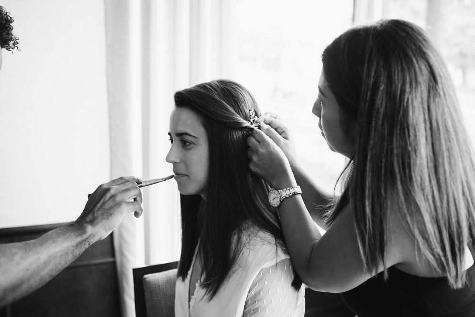 bride having makeup artist apply her lipstick while hair clip is being placed in hair by stylist Toronto wedding photographer