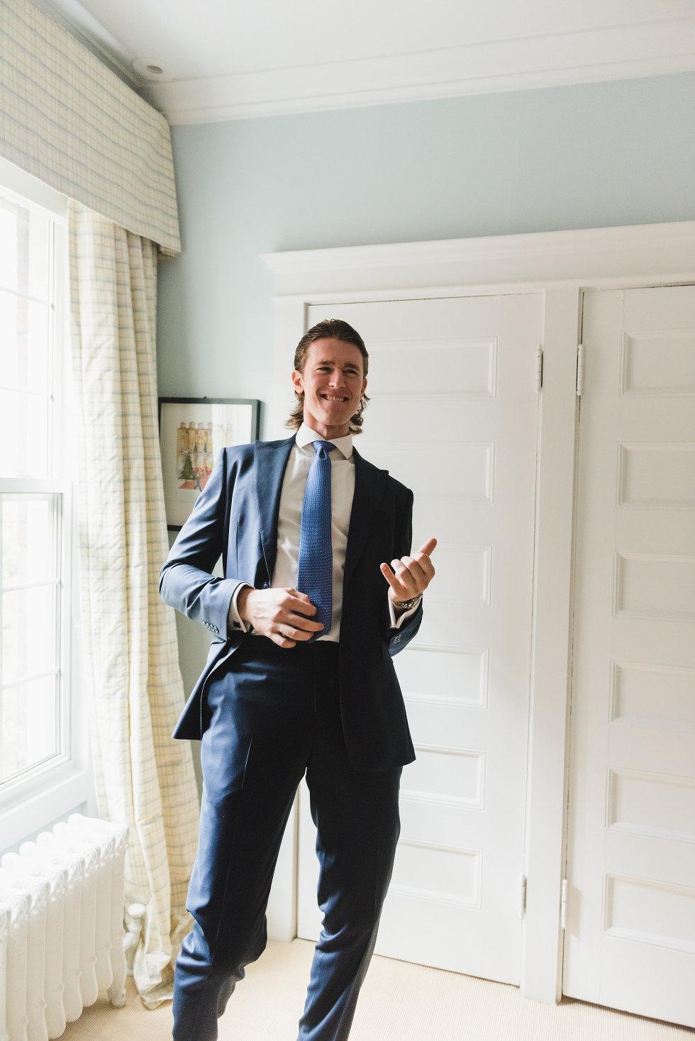 groom standing next to window doing an air guitar Toronto wedding photographer