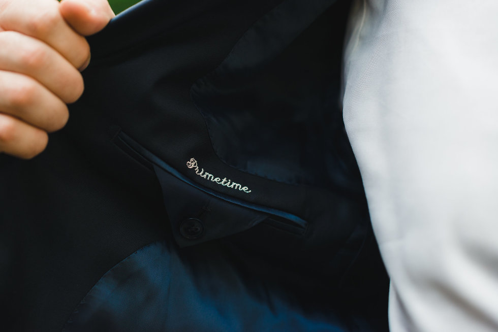 man holding open suit jacket to reveal embroidery Toronto wedding photographer