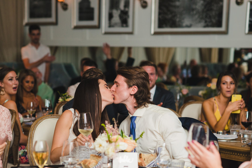 wedding guests seated around bride and groom as they kiss Toronto wedding photography
