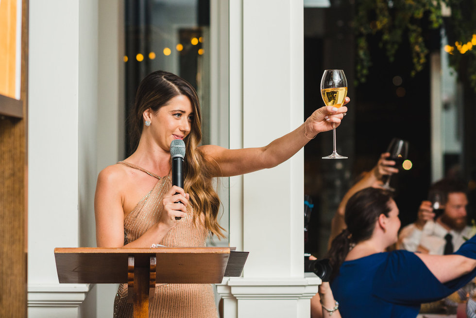 bridesmaid delivers speech into microphone at podium while raising wine glass for a toast Toronto wedding photography