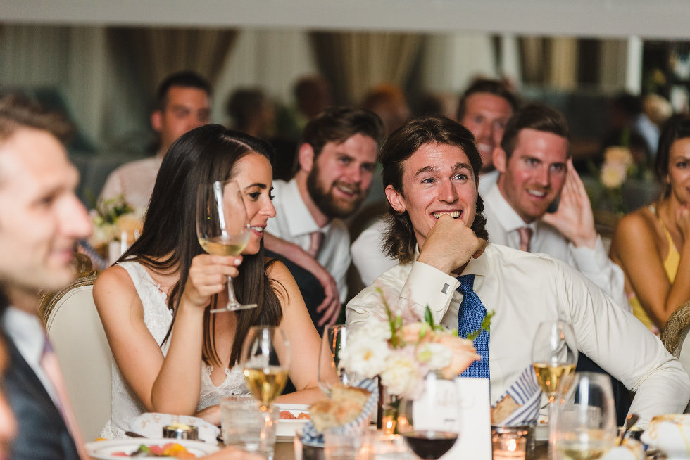 wedding guests seated around bride holding wine glass and smiling groom Toronto wedding photography