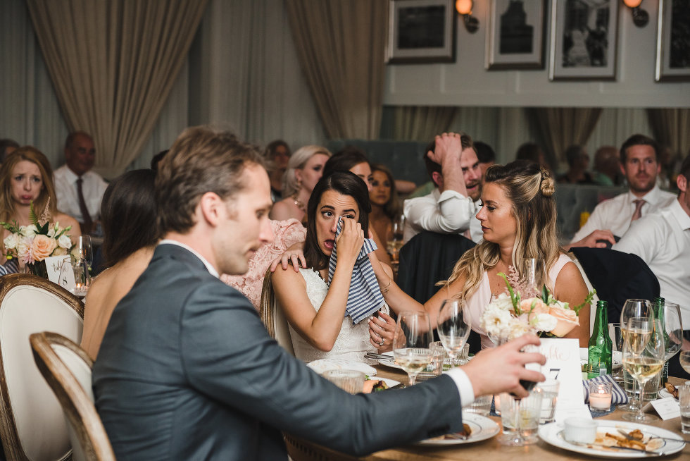 bride seated at table wiping away tears from face with a napkin Toronto wedding photography