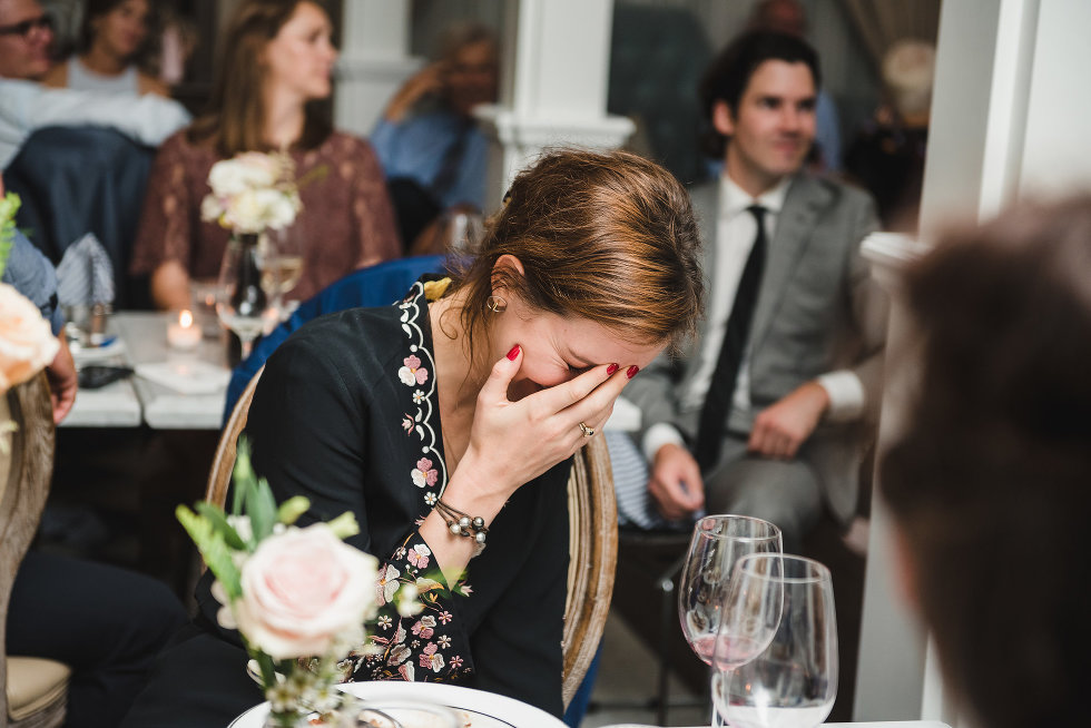 a wedding guest seated while hunched over with her face in her hands Toronto wedding photography